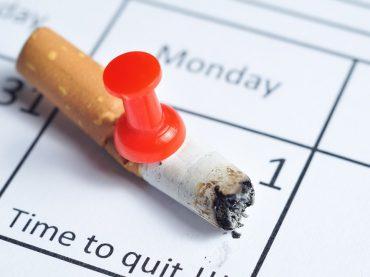 20718327 - cigarette impaled on calendar
