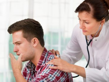 14655276 - female doctor examines a young man colds